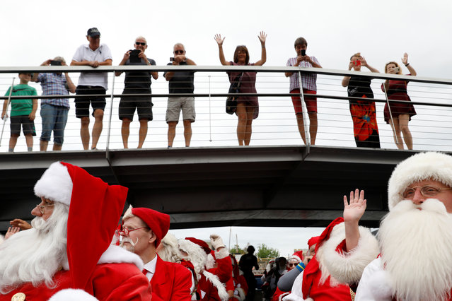 People wave from a bridge toward people dressed as Santa Claus pass on a canal boat during the World Santa Claus Congress, an annual event held every summer in Copenhagen, Denmark, July 23, 2018. (Photo by Andrew Kelly/Reuters)