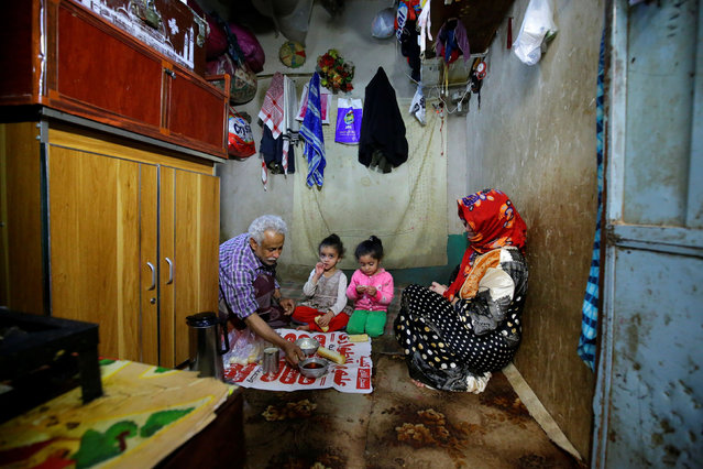 Ahmad Farea and his family sit for a meal at their house in Sanaa, Yemen on February 25, 2021. (Photo by Nusaibah Almuaalemi/Reuters)