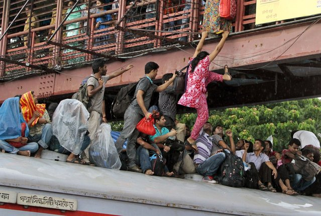A Bangladeshi woman tries to jump onto an overcrowded train from a bridge to travel home for Eid al-Fitr in Dhaka, Bangladesh, Wednesday, August 7, 2013. Muslims across the world are preparing for the arrival of Eid al-Fitr, the festival marking the end of the Muslim fasting month of Ramadan. (Photo by A. M. Ahad/AP Photo)