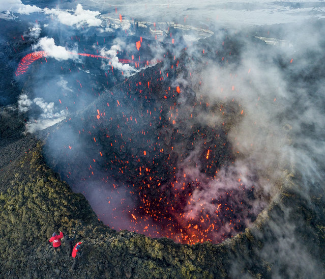 A picture taken with a drone on March 16, 2021 shows members of a local search and rescue squad taking pictures of Klyuchevskoy volcano eruption on Russia's far eastern Kamchatka peninsula. The eruption of a volcano on a Russian peninsula has attracted thrill-seeking tourists risking their lives for picturesque photos, prompting concerns in recent days from local emergency responders. (Photo by Maxim Fesyunov/AFP Photo)