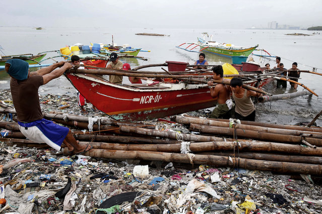 Fishermen carry their boat up on the shore after breaking off its mooring in turbulent floodwaters following overnight southwest monsoon rains brought about by a tropical storm for the second day Wednesday, July 18, 2018, in Bacoor, south of Manila, Philippines. Floodwaters have receded Wednesday in Manila but local authorities still suspended classes as well as some work in Government offices. (Photo by Bullit Marquez/AP Photo)