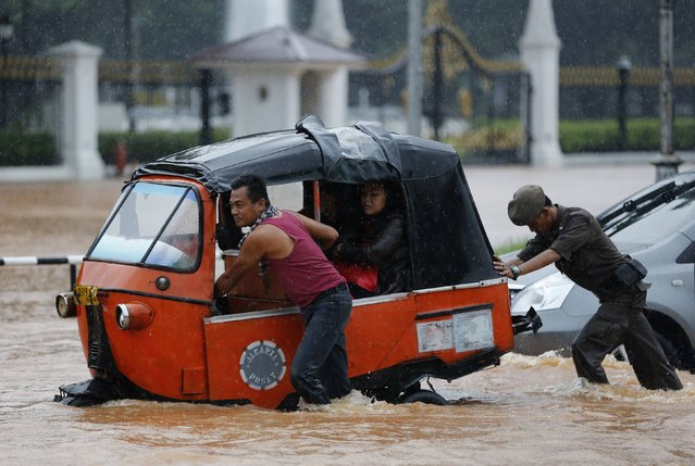 A driver pushes his Baja vehicle through flood waters outside the Presidential Palace, after heavy seasonal rains flooded parts of Jakarta February 9, 2015. (Photo by Darren Whiteside/Reuters)
