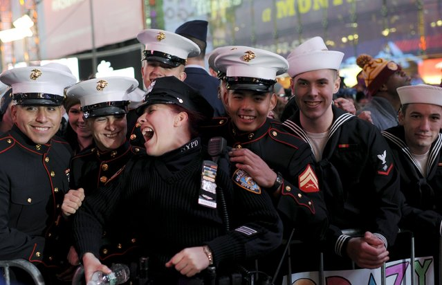 New York Police Department officer Nydia Rodriguez laughs with members of the U.S. Marine Corps and U.S. Navy during New Year's celebrations in Times Square in the Manhattan borough of New York December 31, 2015. (Photo by Darren Ornitz/Reuters)