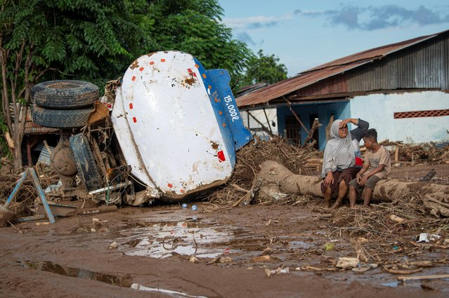 People sit near a damaged truck following flash floods triggered by a tropical cyclone in East Flores, East Nusa Tenggara province, Indonesia, April 6, 2021. (Photo by Aditya Pradana Putra/Antara Foto via Reuters)