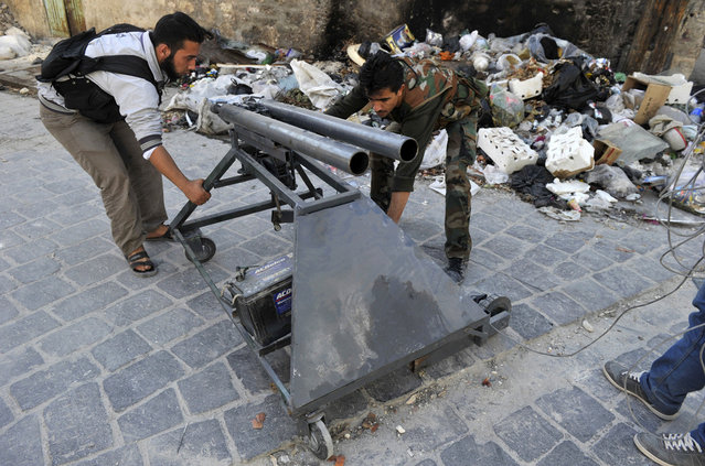 Syrian rebels adjust a homemade mortar launcher in the northern city of Aleppo, on October 16, 2012. (Photo by Tauseef Mustafa/AFP Photo)