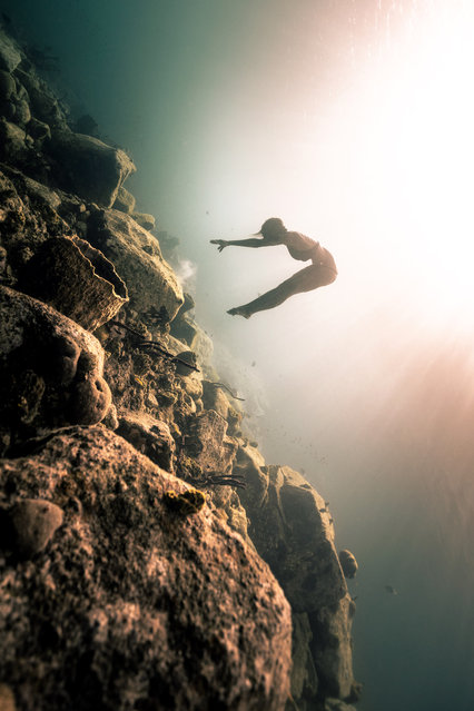 A diver swims in a picturesque location. (Photo by Alex Voyer/Caters News Agency)