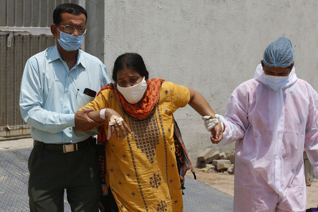 A health worker, right, and a relative helps a patient shift her from a dedicated COVID hospital to another hospital to vacate the bed for new patients, at Civil hospital in Ahmedabad, India, Tuesday, April 13, 2021. New infections have surged in the past month and India has now reported over 13.6 million cases, pushing its toll past Brazil, and making it second only to the United States. In the past 24 hours, over 160,000 new infections have been detected and experts fear that the worst is yet to come. (Photo by Ajit Solanki/AP Photo)