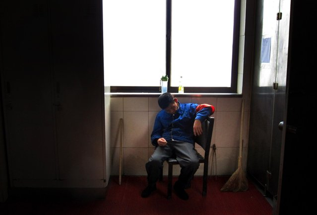 A cleaner sleeps while sitting on a chair at the Beijing West railway station October 28, 2012. (Photo by David Gray/Reuters)