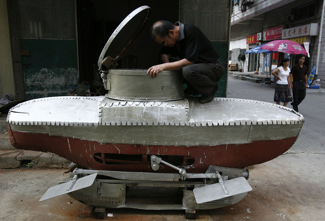 "Li Yuming, a local farmer who is interested in scientific invention, works on his unfinished miniature submarine ""Xiaguang V"" on the outskirts of Wuhan, capital of central China's Hubei province August 24, 2007. ""Xiaguang V"", which is 3-metre long, 1.2-metre in height, has a maximum diving depth of 20 metres, and can hold two adults and one child at the same time. The submarine will be used for tour after safety test, local media said. (Photo by Reuters/Stringer)"