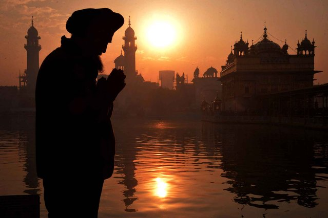An Indian Sikh devotee pays respects on the first day of the year at the Golden Temple in Amritsar on January 1, 2016. (Photo by Narinder Nanu/AFP Photo)