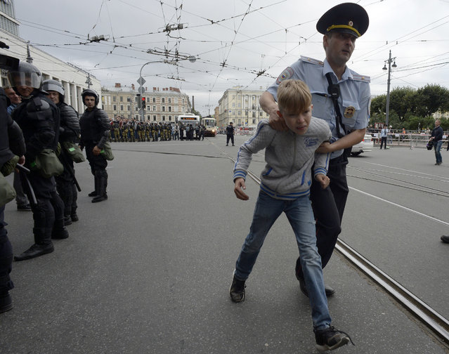 Russian police escorts a youth aware during a protest rally against planned increases to the nationwide pension age in Saint Petersburg on September 9, 2018. Plans to hike the retirement age have led to a rare outburst of public anger and seen President Vladimir Putin's approval ratings take a hit, despite some efforts to water down the changes. But discontent is unlikely to translate into upsets at the ballot box, with serious opposition candidates in the highest-profile Moscow mayoral vote barred from standing.  At least 2,000 people rallied in central Moscow, an AFP correspondent said, as the capital held a mayoral election the Kremlin-backed incumbent is sure to win. (Photo by Olga Maltseva/AFP Photo)