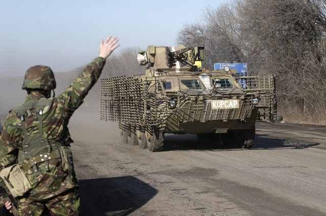 A Ukrainian government troop waves to a armored vehicle driving on the road towards Debaltseve near the town of Artemivsk, Ukraine, Friday, February 13, 2015. (Photo by Petr David Josek/AP Photo)