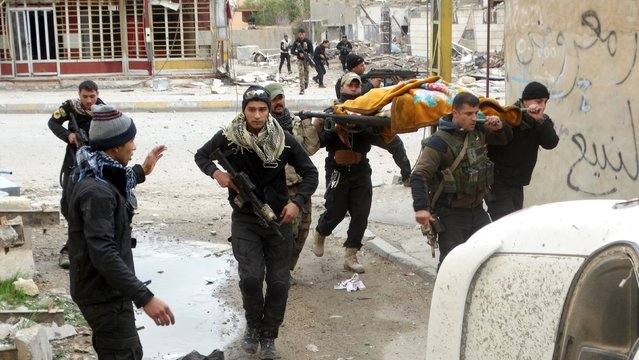 Iraqi security forces and pro-government Sunni tribal fighters carry the body of a woman killed in Ramadi city, Iraq January 4, 2016. (Photo by Reuters/Stringer)