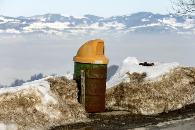 An old oil barrel is used as a rubbish bin beside a mountain road near the village of Schindellegi south of Zurich February 13, 2015. (Photo by Arnd Wiegmann/Reuters)