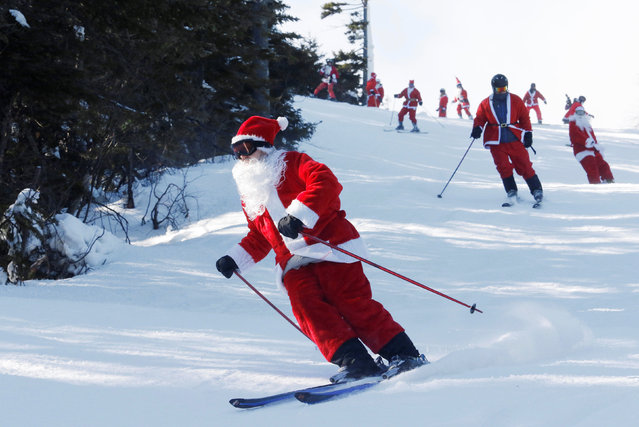Skiers and snowboarders dressed as Santa participate in a charity run down a slope at Sunday River Ski Resort in Newry, Maine, U.S. December 4, 2016. (Photo by Joel Page/Reuters)