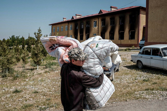 A Kyrgyz man carries belongings in the village of Maksat, near the border with Tajikistan on May 2, 2021. Kyrgyzstan's leader Sadyr Japarov called citizens to respect a peace deal signed with Tajikistan after the pair's heaviest border clashes left at least 34 Kyrgyz citizens dead and said a ceasefire with Tajikistan was holding on May 2, as it accused citizens from its Central Asian neighbour of crimes during the pair's worst clashes at their contested border in decades. The Kyrgyz interior ministry said that casualties on its side had risen to over 160 with 34 deaths, 31 of whom were civilians. (Photo by Danil Usmanov/AFP Photo)