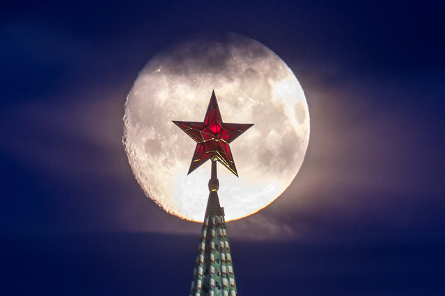 A star atop the Vodovzvodnaya Tower of the Moscow Kremlin is seen against a full moon in Moscow, Russia on April 25, 2021. (Photo by Marina Lystseva/TASS)