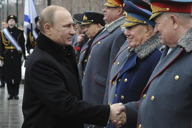 Russian President Vladimir Putin (L) shakes hands with participants as he attends a wreath-laying ceremony to mark the Defender of the Fatherland Day at the Tomb of the Unknown Soldier by the Kremlin walls in central Moscow February 23, 2015. (Photo by Mikhail Klimentyev/Reuters/RIA Novosti/Kremlin)