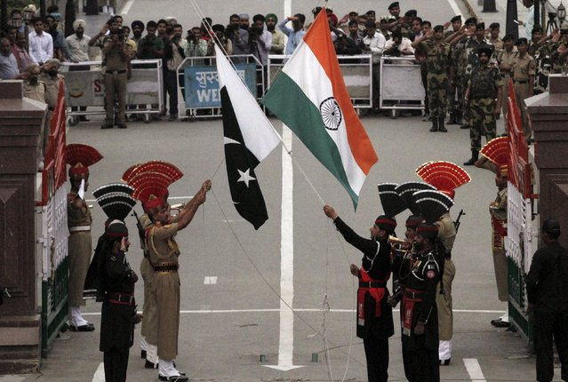 Pakistani rangers (wearing black uniforms) and Indian Border Security Force (BSF) officers lower their national flags during a daily parade at the Pakistan-India joint check-post at Wagah border near Lahore, Pakistan, in this November 3, 2014 file photo. (Photo by Mohsin Raza/Reuters)