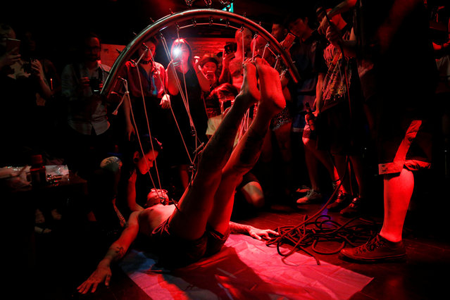 Angus Shen prepares to be suspended from hooks pierced through his skin by professional body artist Wei Yilaien at a bar in Shanghai, China on September 16, 2018. (Photo by Aly Song/Reuters)