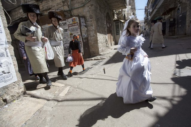 Ultra-Orthodox Jewish youths walk next to a girl in costume during Purim celebrations in Jerusalem, Friday, March 6, 2015. The festival of Purim commemorates the rescue of Jews from genocide in ancient Persia recorded in the biblical Book of Esther. (AP Photo/Sebastian Scheiner)