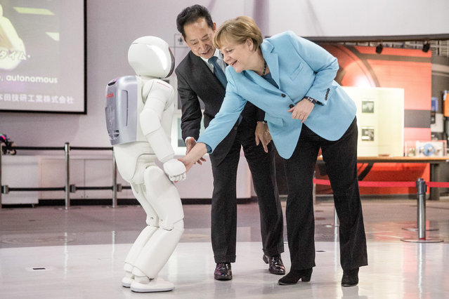 German Chancellor Angela Merkel (R) gets to know the robot Asimo (Advanced Step in Innovative Mobility) at the Miraikan Museum of Emerging Science and Innovation in Daiba, Tokyo, Japan, 09 March 2015. In center the museum's director Mamoru Mohri. Merkel is in Japan for a two-day visit.  EPA/MICHAEL KAPPELER