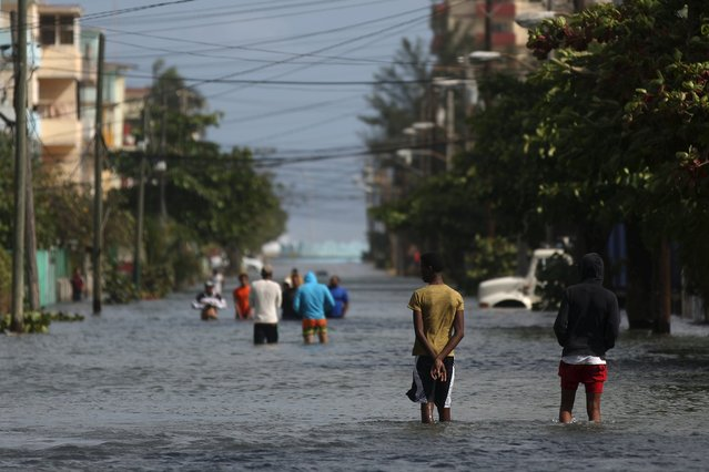 People make their way on a flooded street in Havana, January 23, 2016. (Photo by Alexandre Meneghini/Reuters)