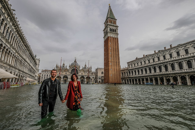 "A couple of tourists walk in ""Piazza San Marco"" on October 29, 2018 in Venice, Italy. (Photo by Stefano Mazzola/Awakening/Getty Images)"