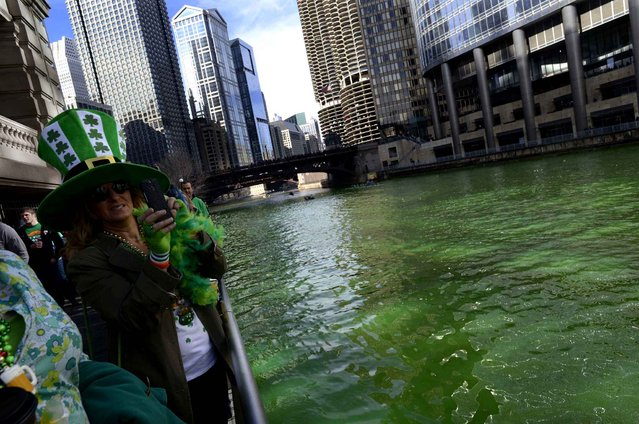 Spectators watch as the Chicago River is dyed green ahead of the St. Patrick's Day parade in Chicago, Saturday, March 14, 2015. (Photo by Paul Beaty/AP Photo)