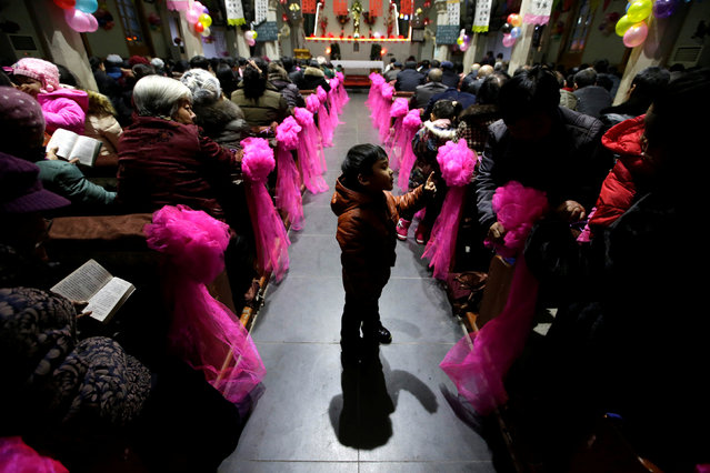 A 5-year-old boy plays during a Christmas eve mass at a Catholic church on the outskirts of Taiyuan, North China's Shanxi province, December 24, 2016. (Photo by Jason Lee/Reuters)