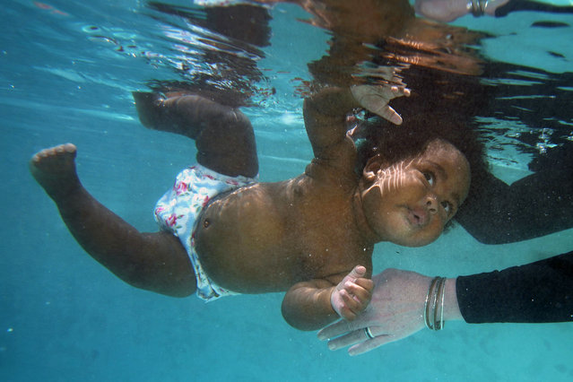 Six-month-old Thyme Allen tuns and begins to float with the help of swimming instructor Tracey Panzer-Michelle during an infant survival swim class Thursday, June 24, 2021, in Richardson, Texas. (Photo by L.M. Otero/AP Photo)