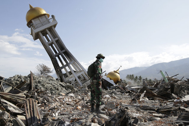 In this Saturday, October 6, 2018, file photo, an Indonesian trooper stands beside a toppled mosque as recovery efforts continue at the earthquake-hit Balaroa neighborhood in Palu, Central Sulawesi, Indonesia. (Photo by Aaron Favila/AP Photo)
