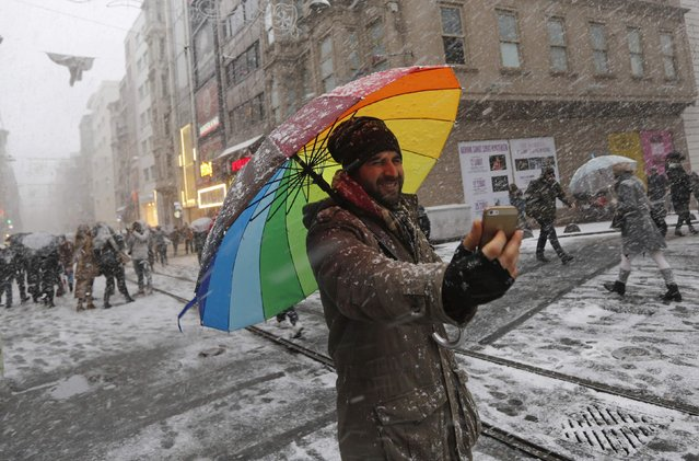 "A street vendor, selling umbrellas, takes a ""selfie"" as snow falls in the main pedestrian street of Istiklal in central Istanbul February 17, 2015. (Photo by Murad Sezer/Reuters)"