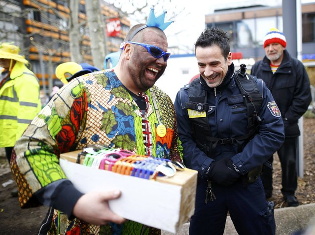 """A police officer wearing a new so-called """"body-cam"""" laughs with a reveller selling sunglasses during the traditional """"Weiberfastnacht"""" (Women's Carnival) celebration in Mainz, Germany, February 4, 2016. (Photo by Kai Pfaffenbach/Reuters)"""
