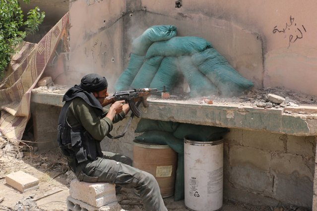 A rebel fighter of Jaysh al-Islam (Army of Islam) fires his weapon in Deir Salman frontline, near the highway of Damascus international airport, after what the rebels said were advances they made in the area following clashes with forces loyal to Syria's President Bashar al-Assad May 11, 2015. (Photo by Amer Almohibany/Reuters)
