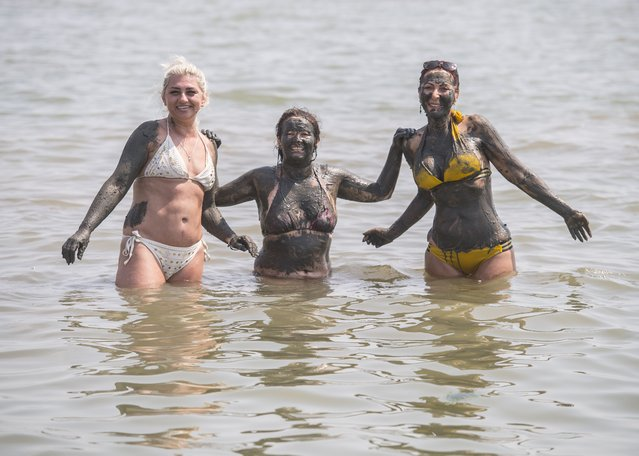 Three women cover themselves in mud while enjoying the hot weather at Southend beach, Essex in southeast England on Wednesday, July 21, 2021. (Photo by Ian West/PA Images via Getty Images)
