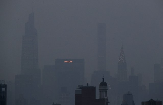 The Met Life and Chrysler buildings glow through a thick haze hanging over Manhattan, Tuesday, July 20, 2021, in New York. Wildfires in the American West, including one burning in Oregon that's currently the largest in the U.S., are creating hazy skies as far away as New York as the massive infernos spew smoke and ash into the air in columns up to six miles high. (Photo by Julie Jacobson/AP Photo)