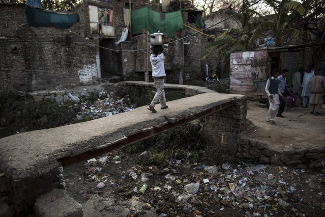 A boy carries a cooking pot on his head as he walks above an open sewer at a slum in Islamabad March 12, 2015. (Photo by Zohra Bensemra/Reuters)