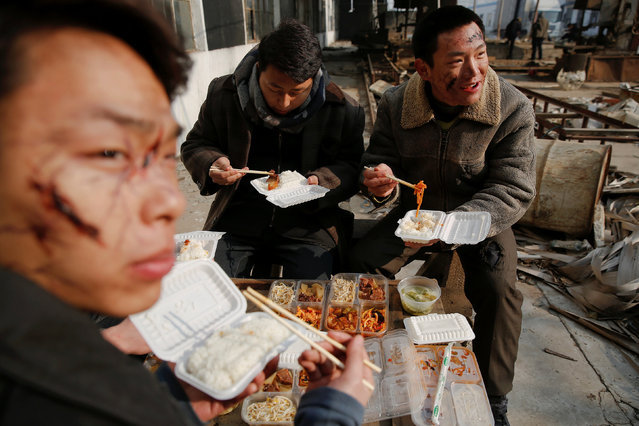 Actors eat lunch at the set of the post-apocalyptic movie Zombie Era at an abandoned factory complex in Langfang, Hebei province, China December 16, 2016. (Photo by Damir Sagolj/Reuters)