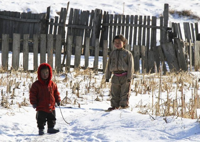 North Korean children stand after snowfall along the banks of the Yalu River, near the North Korean Sakchu County, December 17, 2014. (Photo by Jacky Chen/Reuters)