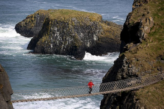 A tourist makes his way across Carrick-a-Rede Rope Bridge on the Causeway coast, north of Belfast April 8, 2015. (Photo by Cathal McNaughton/Reuters)