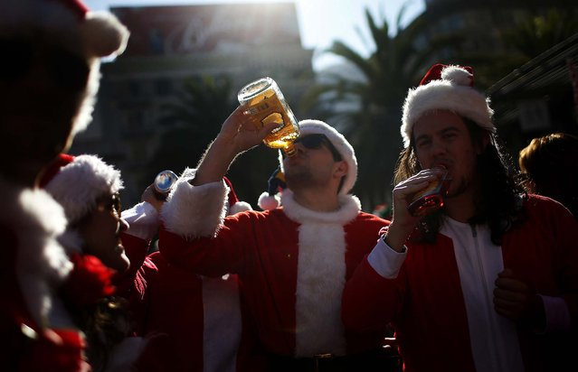 Holiday revelers dressed as Santa Claus drink in Union Square during the annual SantaCon event in San Francisco. (Photo by Stephen Lam/Reuters)