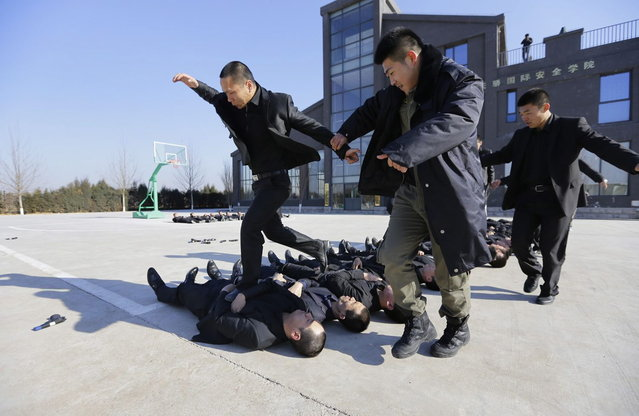 Students run over the bodies of fellow trainees at the Tianjiao Special Guard/Security Consultant training camp on the outskirts of Beijing December 11, 2013. (Photo by Jason Lee/Reuters)