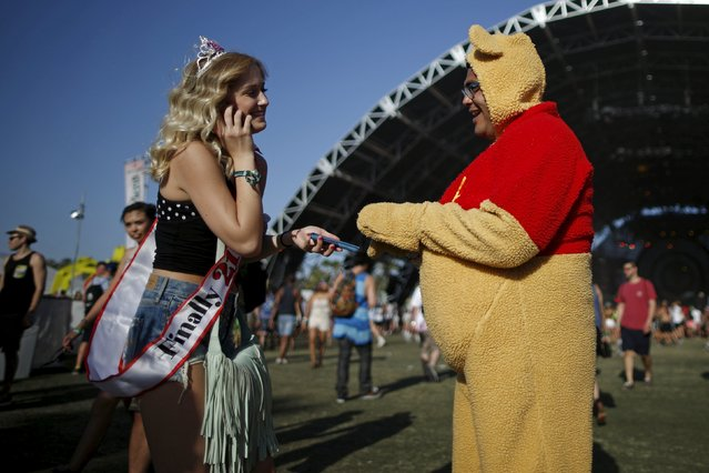A man dressed as Winnie the Pooh talks to a woman celebrating her 21st birthday at the Coachella Valley Music and Arts Festival in Indio, California April 11, 2015. (Photo by Lucy Nicholson/Reuters)