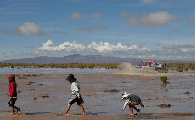 2017 Paraguay-Bolivia-Argentina Dakar rally, 39th Dakar Edition, Eighth stage from Uyuni, Bolivia to Salta, Argentina on January 10, 2017. Children cross a river as Luis Fernando Barbery of Bolivia drives his Toyota with his copilot Salazar Abel. Picture taken January 10, 2017. (Photo by Ricardo Moraes/Reuters)