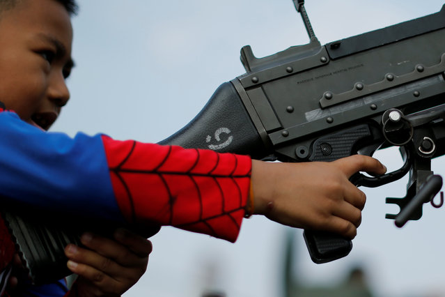 A child plays with a weapon on top of an army vehicle during Children's Day celebration at a military facility in Bangkok, Thailand January 14, 2017. (Photo by Jorge Silva/Reuters)