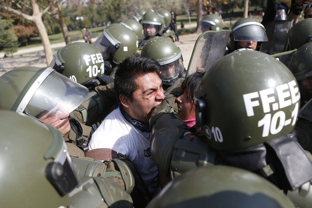A student protester bites a riot policeman while being detained during a riot at a rally demanding Chile's government reform the education system in Santiago. (Photo by Ivan Alvarado/Reuters)