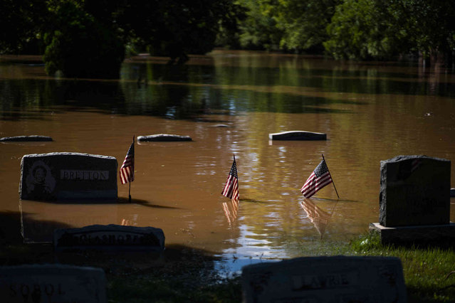 Headstones at a cemetery that flooded are seen in Somerville, N.J. Thursday, September 2, 2021. A stunned U.S. East Coast faced a rising death toll, surging rivers, tornado damage and continuing calls for rescue Thursday after the remnants of Hurricane Ida walloped the region with record-breaking rain, drowning more than two dozen people in their homes and cars. (Photo by Eduardo Munoz Alvarez/AP Photo)