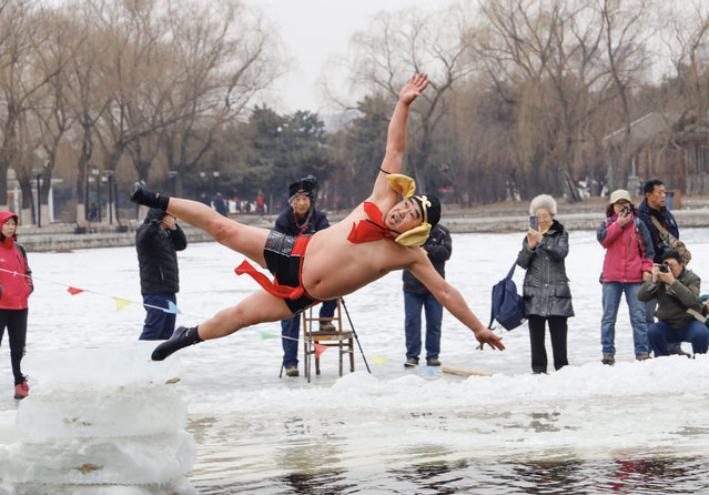 A man wearing a costume dives into a partly frozen lake in Shenyang, in China's northeastern Liaoning province on February 19, 2019. (Photo by AFP Photo/China Stringer Network)