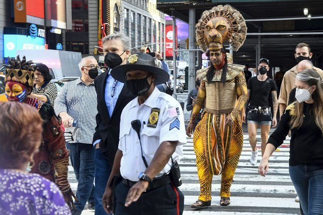 """Costumed cast members of Broadway's """"The Lion King"""", L. Steven Taylor, as Mufasa, right, and and Tshidi Manye, as Rafiki, left, appear in Times Square to herald the return of Broadway theater in New York, Tuesday, September 14, 2021. (Photo by Marc A. Hermann/Metropolitan Transportation Authority via AP Photo)"""